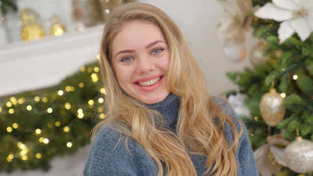 Fashionable smiling woman wearing knitwear cozy sweater in front of christmas tree Banco de Imagens
