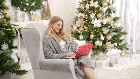 Portrait of smiling woman holding laptop on her laps and working. Sitting on comfortable armchair
