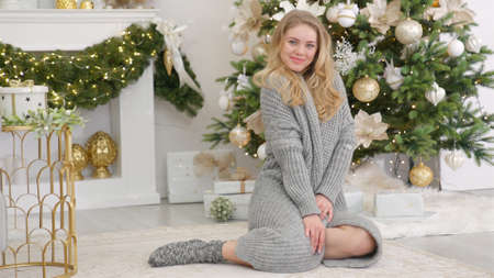 Beautiful young blonde woman in warm winter gray sweater sitting next to christmas tree and chimney