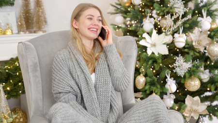Young woman in a nice warm sweater making a Christmas greeting call on her mobile phone Banco de Imagens