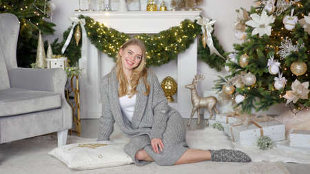 Christmas portrait of a smiling blonde girl in a warm cozy sweater on the background of Christmas Banco de Imagens