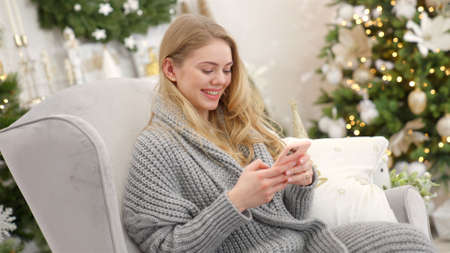 Smiling trendy woman in gray cozy sweater sittin on comfortable armchair and sending text message