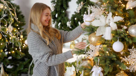 Happy young blond woman decorating christmas tree with ball at her home Banco de Imagens