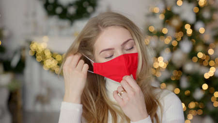 Tired woman take off protective face mask while standing in festive decorated home for Christmas