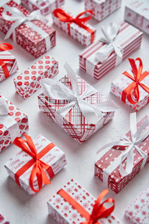 Colorful white and red Christmas theme. Wrapped gifts in festive paper with ribbon Zdjęcie Seryjne