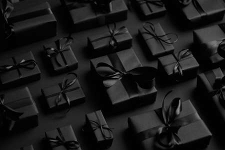 Elegant black Christmas theme. Wrapped gifts in black matte paper with ribbon
