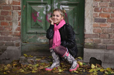 house coat: The smiling girl in rubber boots with a ridiculous hairdress sits on a threshold of the old house