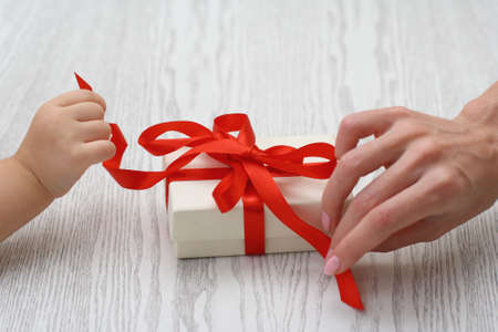 Child and woman hands opening a gift Stock Photo - 5975504