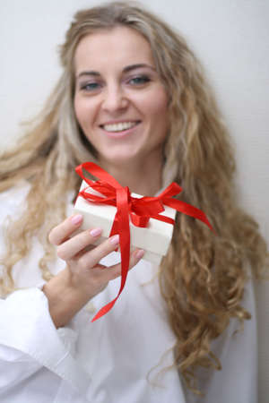 Young woman holds present box with red ribbon Stock Photo - 5975506