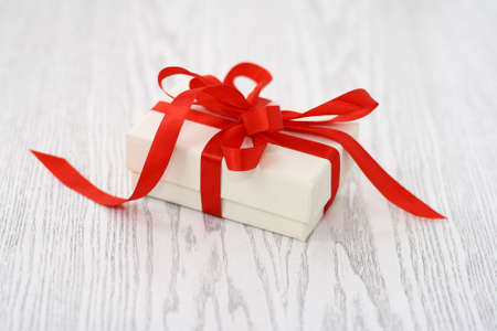 Present box with red ribbon on the wooden background Stock Photo - 5975527