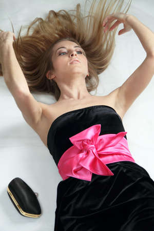 Beautiful blonde girl in black dress with pink bow photo