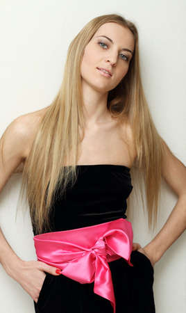 Beautiful blonde girl in black dress with pink bow Stock Photo - 6534075