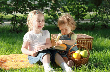 Two small lovely girls with fruits and book in the park photo