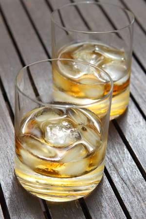 Close-up of a two glasses of whiskey on the wooden table  photo
