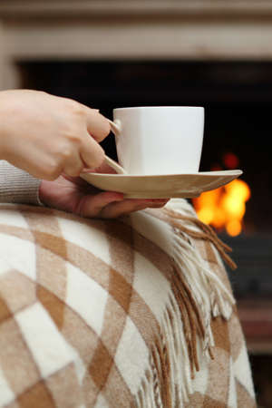 Woman having tea by the fireplace photo