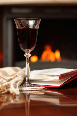 Red wine, book and shawl by the fireplace photo
