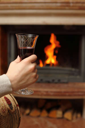 Man having red wine by the fireplace photo