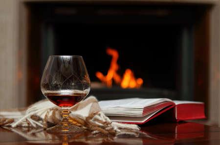 vin chaud: Cognac, livre et châle par la cheminée.