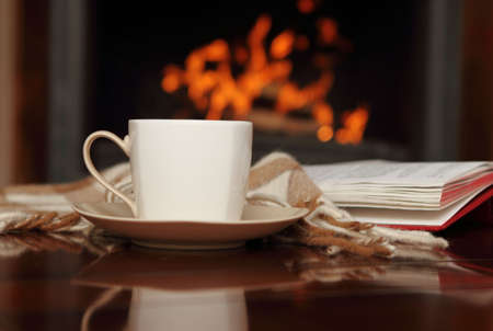 cosy: Tea, book and shawl by the fireplace Stock Photo