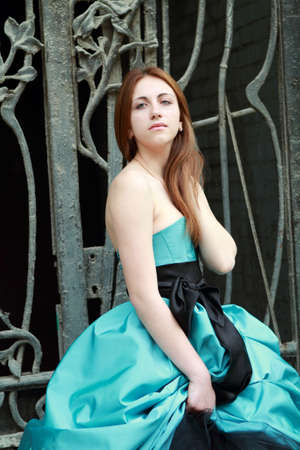 Romantic girl in the beautiful dress near the fence photo