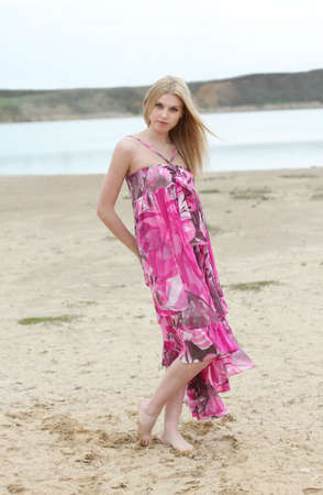 Beautiful blond girl in pink on the beach photo