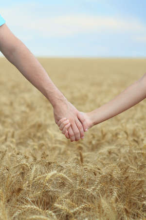 Young couple holding hands in the field. Close-up Stock Photo - 7310090