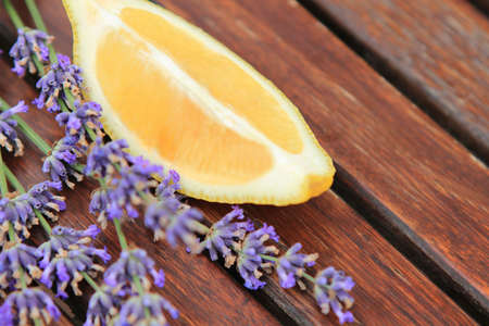 Lemon with lavender flowers on the wooden table. Close up photo
