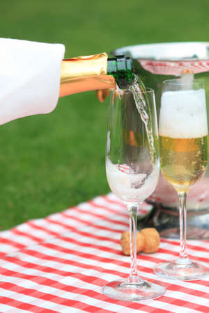 Champagne being poured to glasses at a summer picnic photo