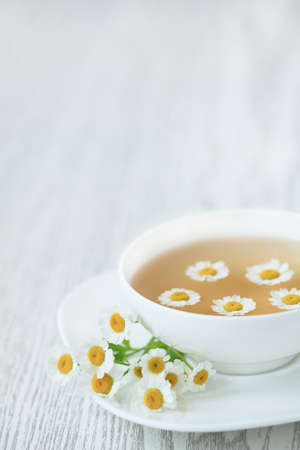 Cup with tea of chamomile on wooden background photo