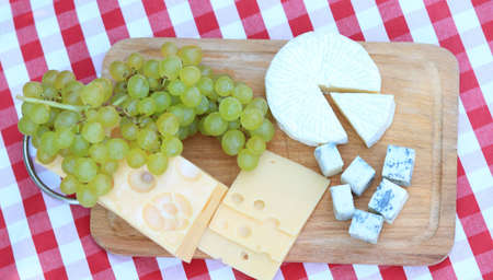 Various sorts of cheese with white grapes photo
