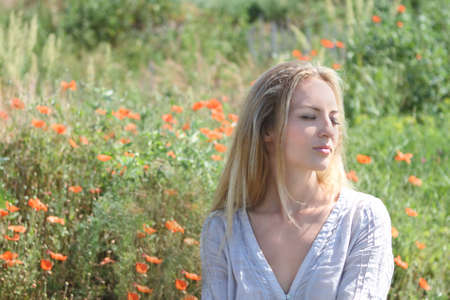 Beautiful blond girl in the poppy field Stock Photo - 7428882