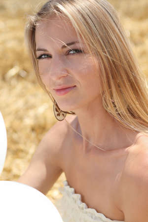 Blond smiling girl with white balloons in the field Stock Photo - 7450444
