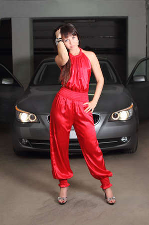 Girl in red near the car in the garage photo