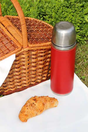 Outdoor picnic setting with red bottles photo