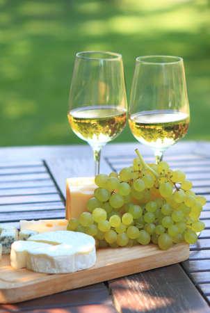 Vari tipi di formaggio, uva e due bicchieri di vino bianco