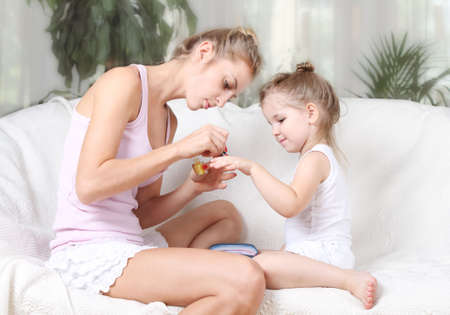Mother and daughter painting their finger nails with polish photo