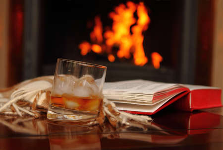 Whiskey, book and shawl by the fireplace