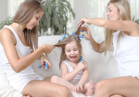 Three girls having fun together playing hair photo
