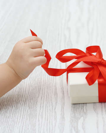 xmas baby: Little hand of the child opening a gift