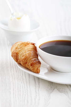 Soft boiled egg, coffee with croissant and jam photo