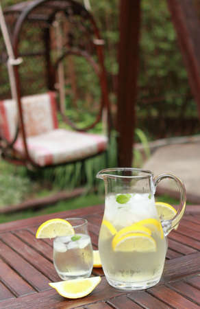 Pitcher and glasses of fresh lemonade in the garden  Stock Photo - 7854841