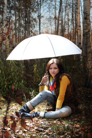 Brunette girl in the forest under light umbrella photo