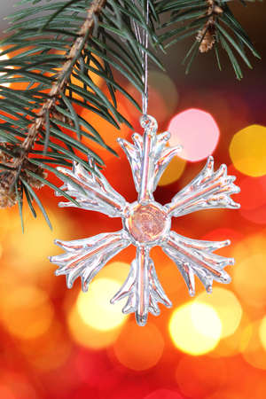 Snowflake on branch of Christmas tree against red blurred background Stock Photo - 8212632