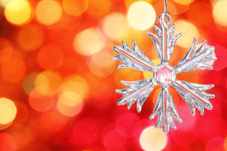 Snowflake on branch of Christmas tree against red blurred background Stock Photo - 8212815