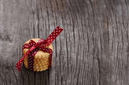 lunares rojos: Las cookies decoraci�n con cinta de topos de rojo oscuro en el fondo de madera Foto de archivo