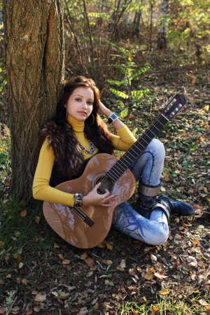 Beautiful brunette guitar player girl in the autumn forest photo