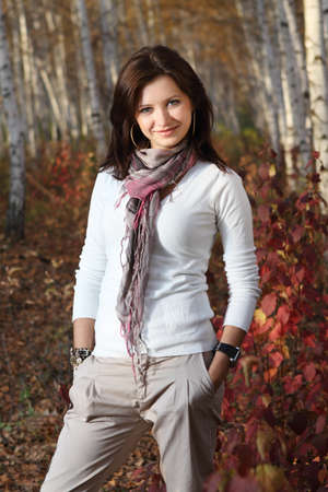 Beautiful smiling brunette girl in autumn forest photo