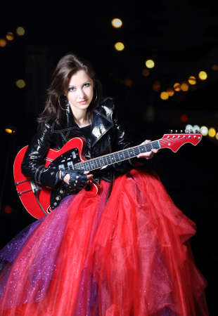 Brunette guitar player girl in the night city photo