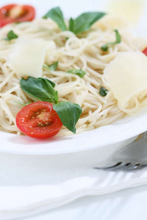 Spaghetti with pesto sauce, cherry tomato and parmesan cheese photo