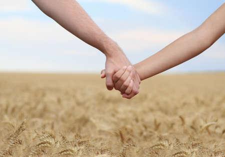 manos juntas: Joven pareja de manos de explotaci�n en el campo. Close-up